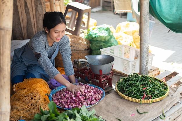 Asiatische gemüsehändlerin lächelt, während sie eine schalotte in einem tablett am gemüsestand hält