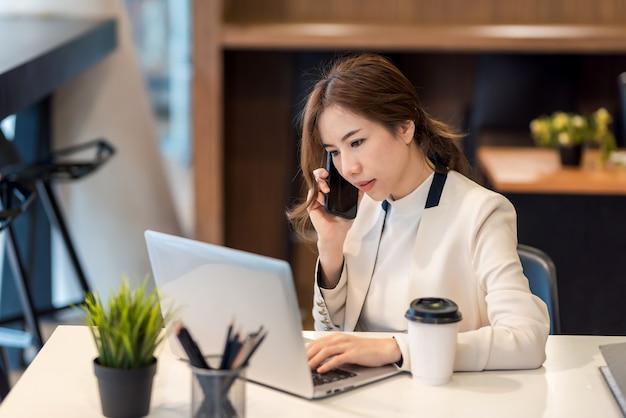 Asiatische geschäftsfrau am telefon sprechen bei der arbeit bereit, auf tablet im büro zu arbeiten.