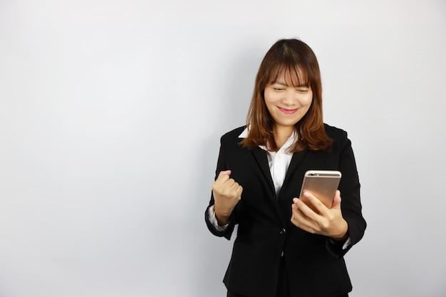 Asiatische geschäftsfrau aufgeregt und überraschung mit etwas am handy auf weiß