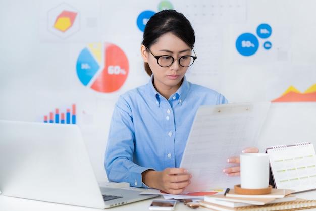 Asiatische geschäftsfrau beachten beim arbeiten geschäfts- und finanzkonzepte.