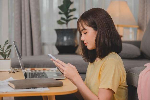 Asiatische geschäftsfrau, die allein zu hause online arbeitet. frauenlebensstil im wohnzimmer. soziale distanzierung und neue normalität.