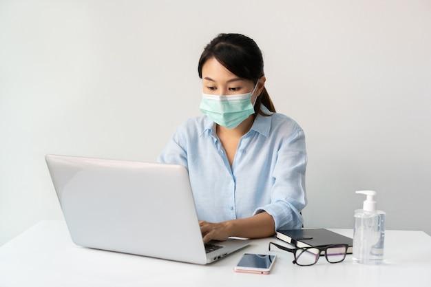 Asiatische geschäftsfrau, die am arbeitsplatz arbeitet und eine gesichtsmaske während der coronavirus-krise trägt