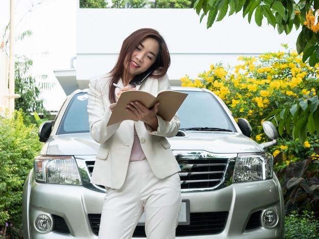 Asiatische geschäftsfrau, die am handy spricht und anmerkungen gegen ein auto macht.