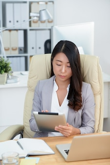 Asiatische geschäftsfrau, die am schreibtisch im büro sitzt und tablette verwendet