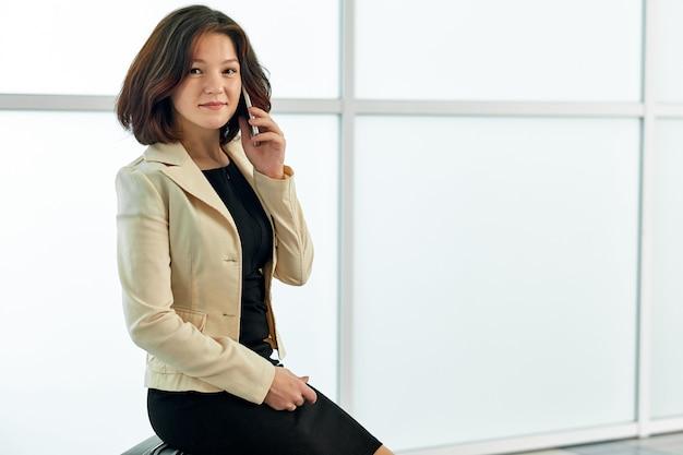 Asiatische geschäftsfrau, die am telefon spricht. portrait der schönen frau im büro