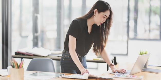 Asiatische geschäftsfrau, die an dem projekt mit laptop arbeitet