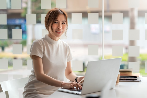 Asiatische geschäftsfrau, die an laptop im büro arbeitet.