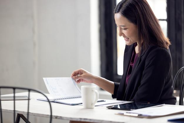 Asiatische geschäftsfrau, die an tischpapieren arbeitet
