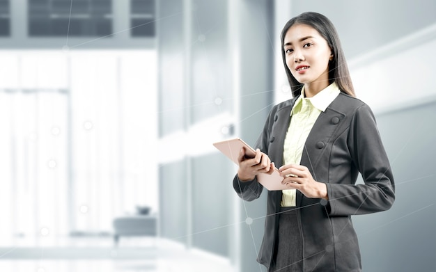Asiatische geschäftsfrau, die beim verwenden der tablette auf dem büroraum steht