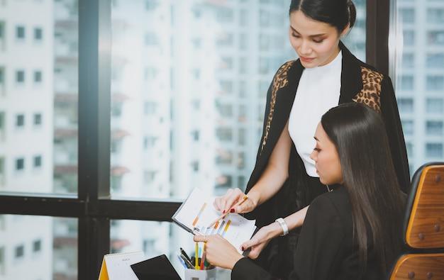 Asiatische geschäftsfrau, die bleistiftpunkt zum analysemarketingbericht und -diagramm mit kollegen im arbeitsplatzbüro verwendet