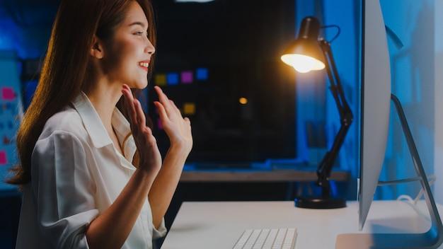 Asiatische geschäftsfrau, die computer verwendet, spricht mit kollegen über plan in videoanruf, während sie nachts von zu hause im wohnzimmer arbeiten. selbstisolation, soziale distanzierung, quarantäne zur vorbeugung von coronaviren.