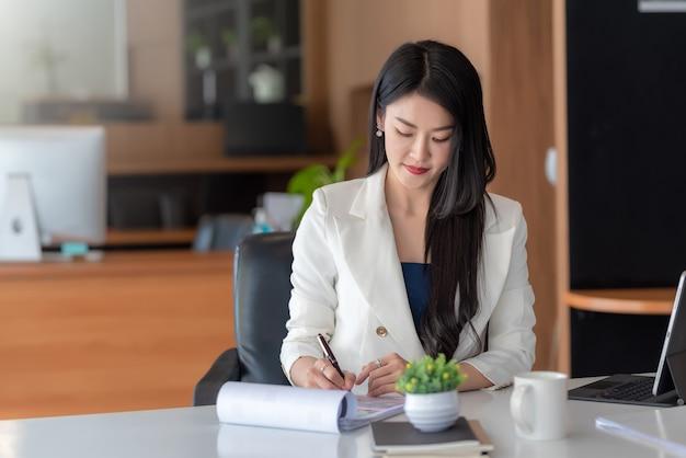 Asiatische geschäftsfrau, die dokumente im büro untersucht.
