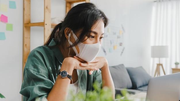 Asiatische geschäftsfrau, die eine medizinische gesichtsmaske mit laptop trägt, spricht mit kollegen über den plan im videoanruf, während sie von zu hause aus im wohnzimmer arbeitet.