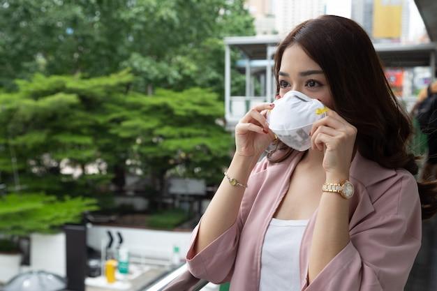 Asiatische geschäftsfrau, die eine schützende gesichtsmaske auf einer stadtstraße mit luftverschmutzung trägt. hygienische gesichtsmaske für das umweltbewusstseinskonzept der sicherheit im freien