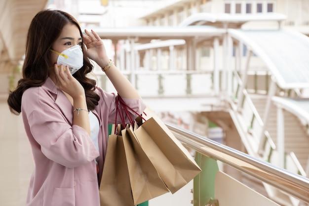 Asiatische geschäftsfrau, die eine schützende gesichtsmaske auf einer stadtstraße mit luftverschmutzung trägt. hygienische gesichtsmaske für die sicherheit im freien umweltbewusstsein