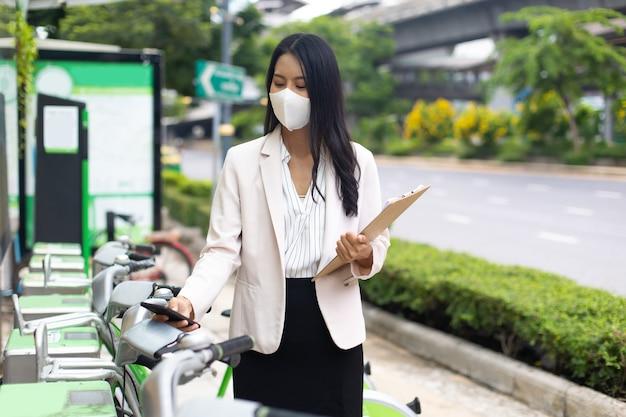 Asiatische geschäftsfrau, die eine schützende gesichtsmaske trägt, verhindert das covid-19-virus mit dem smartphone, um ein öffentliches fahrrad im freien zu mieten. fahrradverleih in stadtumgebung.