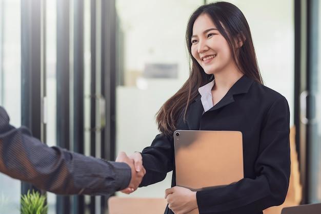 Asiatische geschäftsfrau, die eine tablette hält, die hand mit glücklichem rüttelt. geschäftsleute erfolgreiche zusammenarbeitsvereinbarung im büro.