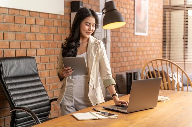 Asiatische geschäftsfrau, die einen computertablett hält und ihren laptop-computer betrachtet