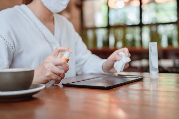 Asiatische geschäftsfrau, die hand und computer vor dem online-woking säubert. soziale distanzierung und neuer normaler lebensstil.
