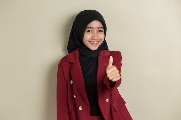 Asiatische geschäftsfrau, die hijab mit hand daumen hoch in ordnung trägt