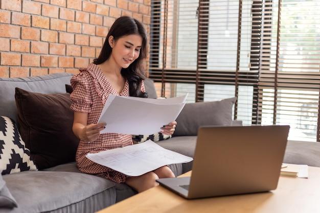 Asiatische geschäftsfrau, die ihre arbeitspläne vor ihrem laptop in ihrem wohnzimmer betrachtet