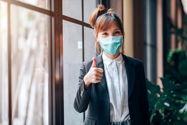 Asiatische geschäftsfrau, die im arbeitsbüro steht und daumen zeigt. sie trägt eine virusschutzmaske zur vorbeugung gegen coronavirus- oder covid-19-ausbrüche - gesundheits- und geschäftskonzept