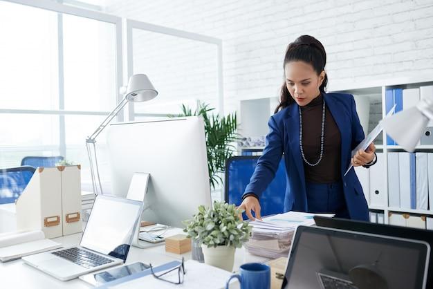 Asiatische geschäftsfrau, die im büro steht und stapel von dokumenten auf schreibtisch betrachtet