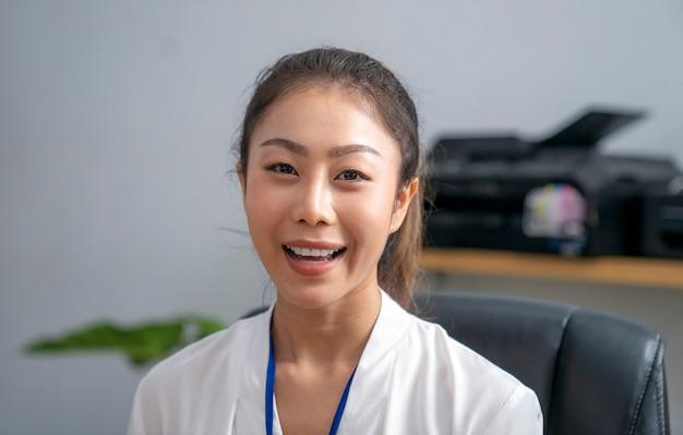 Asiatische geschäftsfrau, die in ihrem büro spricht, dieses bild kann für geschäfts-, online-besprechungskonzept verwenden