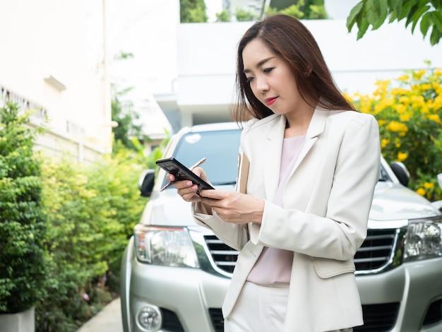 Asiatische geschäftsfrau, die intelligentes telefon gegen ein auto verwendet.