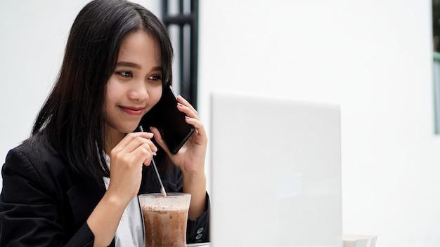 Asiatische geschäftsfrau, die kaffee trinkt und auf smartphone am café spricht