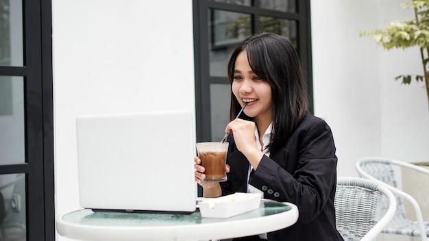 Asiatische geschäftsfrau, die kaffee trinkt und mit seinem laptop im café arbeitet