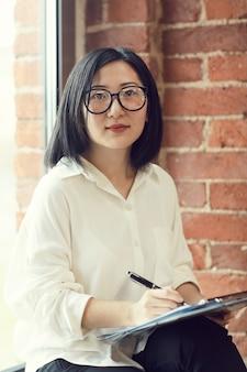 Asiatische geschäftsfrau, die kamera im büro betrachtet