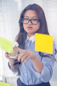 Asiatische geschäftsfrau, die klebrige anmerkungen über wand im büro verwendet