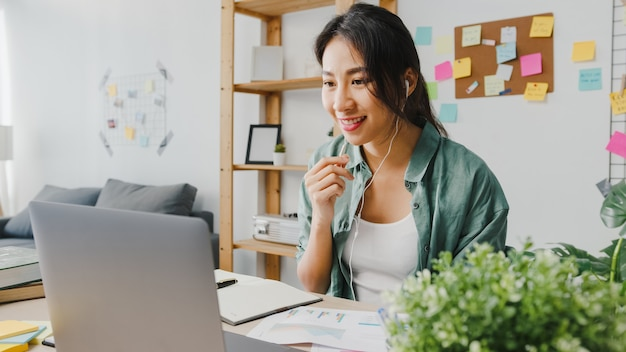 Asiatische geschäftsfrau, die laptop verwendet, spricht mit kollegen über den plan im videoanruf, während sie intelligent von zu hause aus im wohnzimmer arbeitet.