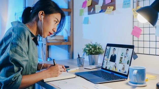 Asiatische geschäftsfrau, die laptop verwendet, spricht mit kollegen über den plan in der videoanrufbesprechung im wohnzimmer.
