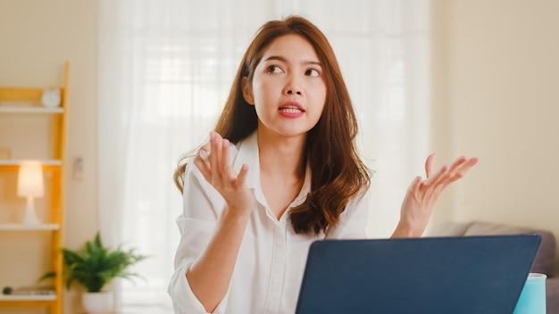 Asiatische geschäftsfrau, die laptop verwendet, spricht mit kollegen über plan in videoanruf, während kluges arbeiten von zu hause im wohnzimmer. selbstisolation, soziale distanzierung, quarantäne zur vorbeugung von coronaviren.