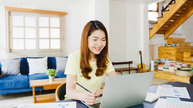 Asiatische geschäftsfrau, die laptop verwendet, spricht mit kollegen über plan in videoanruf, während kluges arbeiten von zu hause im wohnzimmer. selbstisolation, soziale distanzierung, quarantäne zur vorbeugung von koronaviren.