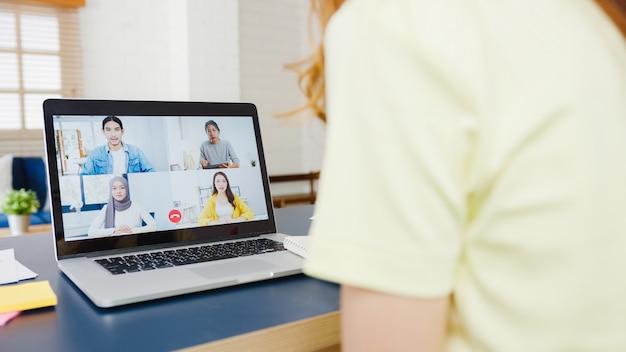 Asiatische geschäftsfrau, die laptop verwendet, spricht mit kollegen über plan in videoanrufbesprechung, während sie von zu hause im wohnzimmer arbeiten. selbstisolation, soziale distanzierung, quarantäne zur vorbeugung von koronaviren.