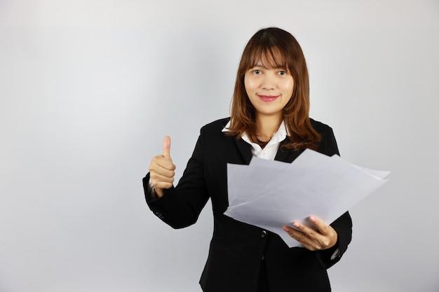 Asiatische geschäftsfrau, die leere papiere beim zeigen des daumens oben auf weiß hält