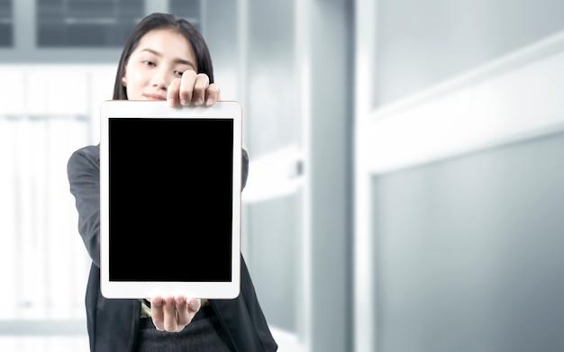 Asiatische geschäftsfrau, die leeren tablettbildschirm auf dem büroraum zeigt. leerer tablet-bildschirm für speicherplatz