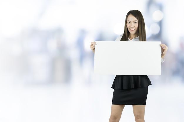 Asiatische geschäftsfrau, die leeres whiteboard auf unscharfem hintergrund nimmt.