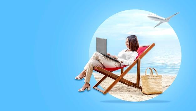 Asiatische geschäftsfrau, die mit dem laptop sitzt im strandstuhl arbeitet