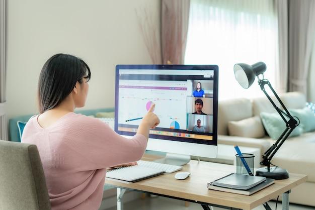 Asiatische geschäftsfrau, die mit ihren kollegen über plan in videokonferenz mit geschäftsteam spricht, das computer für ein online-treffen in videoanruf verwendet.