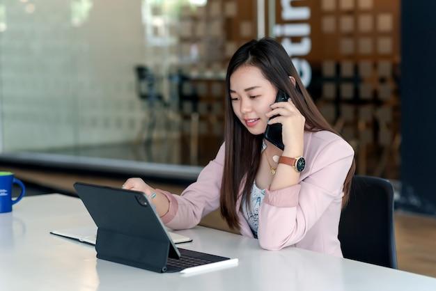Asiatische geschäftsfrau, die mit tablet im büro telefoniert.
