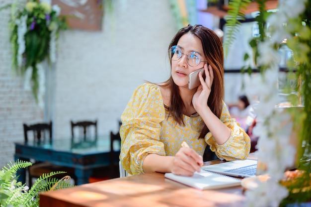 Asiatische geschäftsfrau, die online im café arbeitet. thailändischer frauenlebensstil mit kaffee am wochenende. soziale distanzierung und neue normalität.