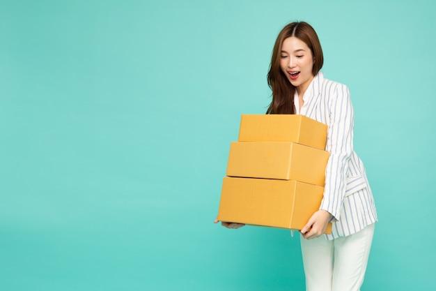 Asiatische geschäftsfrau, die paketpaketkasten lokalisiert auf grünem hintergrund hält
