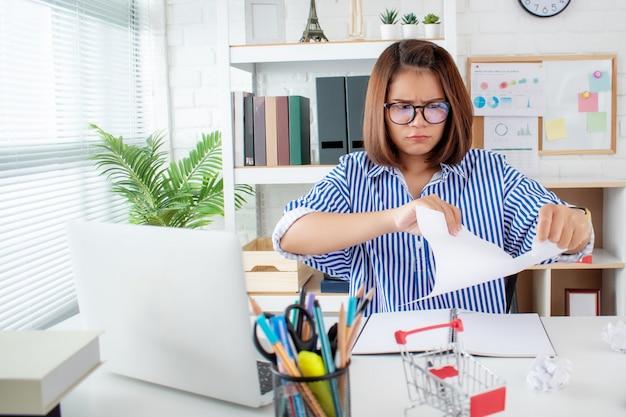 Asiatische geschäftsfrau, die papier zerreißt