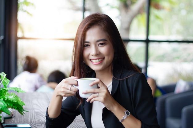 Asiatische geschäftsfrau, die schalenkaffee für das trinken am kaffeecafé lächelt und hält.