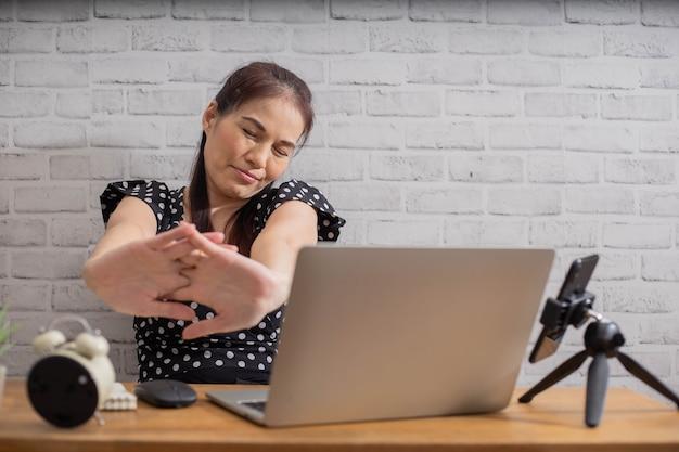 Asiatische geschäftsfrau, die sich ausdehnt und zur entspannung trainiert, während sie zu hause hart arbeitet.