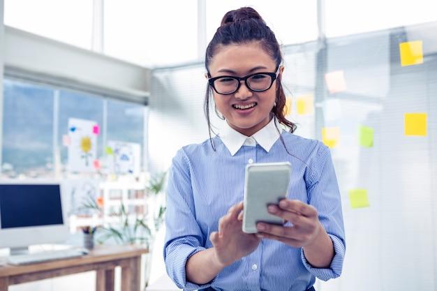 Asiatische geschäftsfrau, die smartphone im büro verwendet